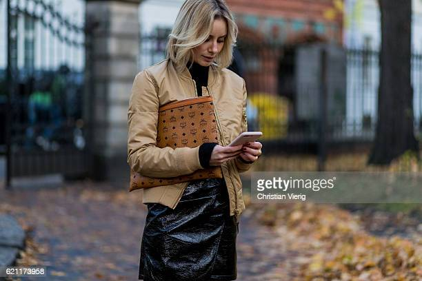 Lisa Hahnbueck writting a text message on her phone wearing a beige Schott Bomber jacket a black HM Trend Mohair Blend Knit a black Mango Asymmetric...