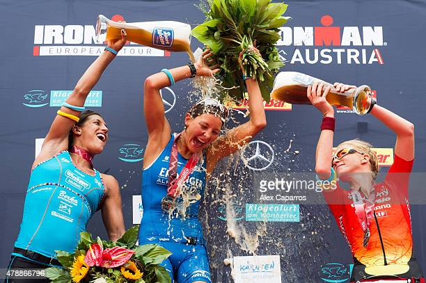 Lisa Hutthaler 2nd place Eva Wutti 1st place and Sarah Piampiano 3rd place celebrate finishing Ironman Klagenfurt by pouring beer ove each other on...