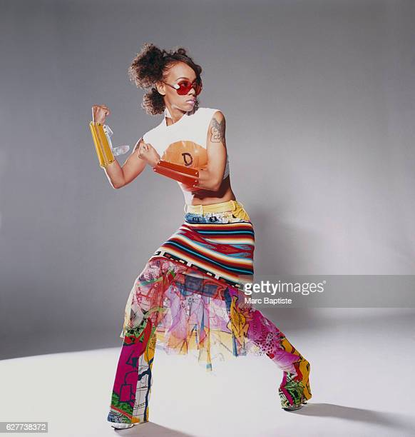 Lisa Left Eye Lopes of the popular RB group TLC She wears a shortsleeved Christian Dior tshirt with a multicolored miniskirt over pants