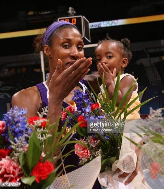 Lisa Leslie of the Los Angeles Sparks and her daughter Lauren throw kisses to the camera following the game against the Minnesota Lynx on July 27...