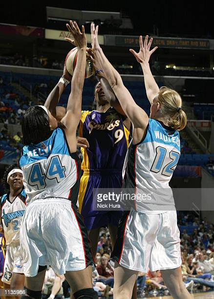 Lisa Leslie of the Los Angeles Sparks gets blocked by the defense of Chasity Melvin and Ann Wauters of the Cleveland Rockers on July 20 2002 at Gund...