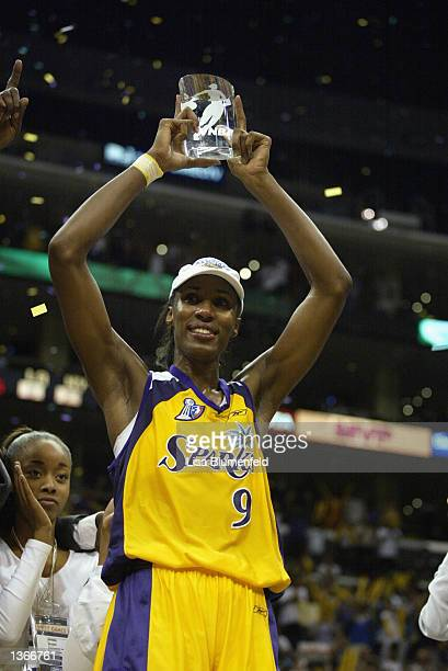 Lisa Leslie of the Los Angeles Sparks holds up the Playoff MVP trophy after Game two of the 2002 WNBA Finals against the New York Liberty on August...