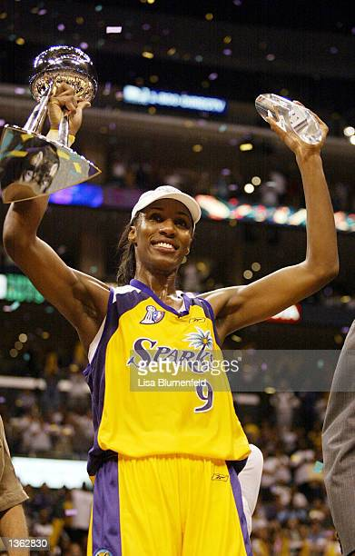 Lisa Leslie of the Los Angeles Sparks holds up the WNBA Championship trophy and the Playoff MVP trophy after game two of the 2002 WNBA Finals against...