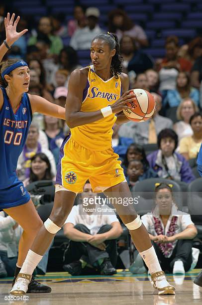 Lisa Leslie of the Los Angeles Sparks looks for the pass under pressure from Ruth Riley of the Detroit Shock on August 19 2005 at Staples Center in...