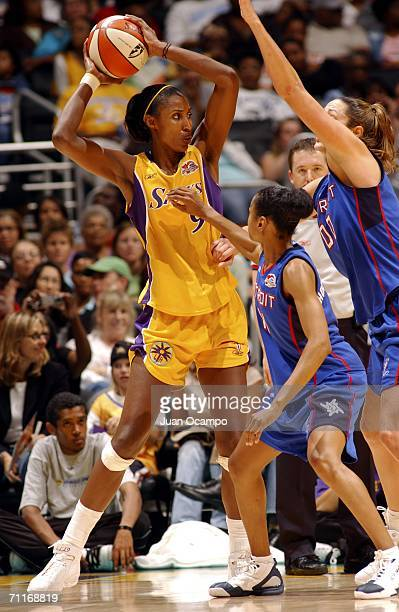 Lisa Leslie of the Los Angeles Sparks looks to pass the ball past Kedra HollandCorn and Ruth Riley of the Detroit Shock during the game at the...
