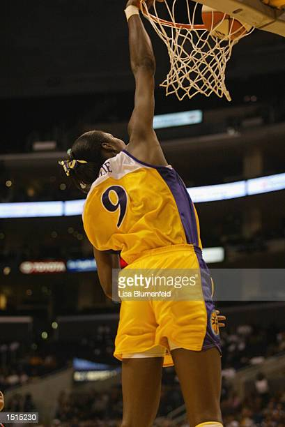 Lisa Leslie of the Los Angeles Sparks records the first ever slam dunk in women's professional basketball during the game against the Miami Sol on...