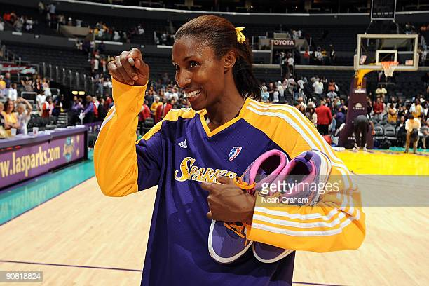 Lisa Leslie of the Los Angeles Sparks seeks out a fan to give a pair of her autographed shoes to after the game against the Minnesota Lynx on...