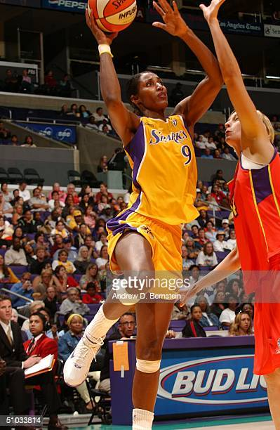 Lisa Leslie of the Los Angeles Sparks shoots past the Phoenix Mercury defense at Staples Center on July 7 2004 in Los Angeles California NOTE TO USER...