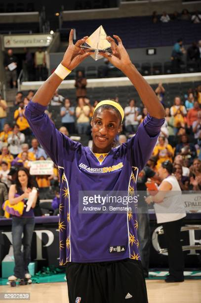 Lisa Leslie of the Los Angeles Sparks shows the crowd her award for Defensive Player of the Year prior to the game against the Seattle Storm on...