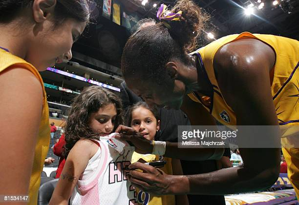 Lisa Leslie of the Los Angeles Sparks signs autographs for a young fan following the victory over the Detroit Shock at Staples Center on June 11,...