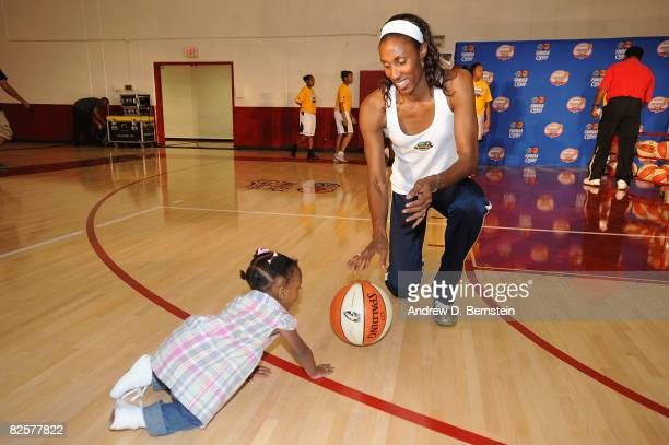Lisa Leslie of the Los Angeles Sparks takes time out to play with daughter Lauren at the Project Rebound clinic on August 27 2008 at Morningside High...