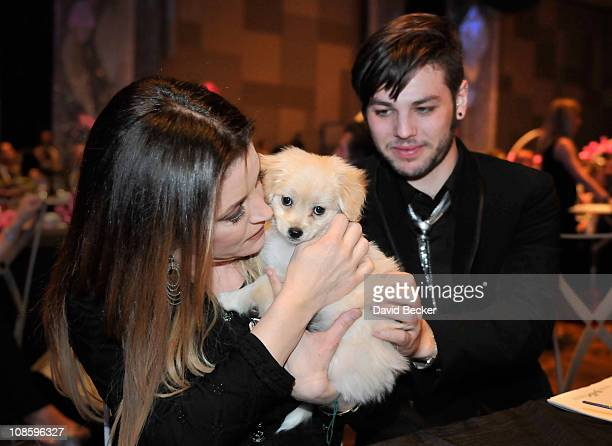 Lisa Marie Presley and Navarone Garibaldi share some cuddle time with a threemonthold cockapoo puppy during annual Black White Ball fundraising event...