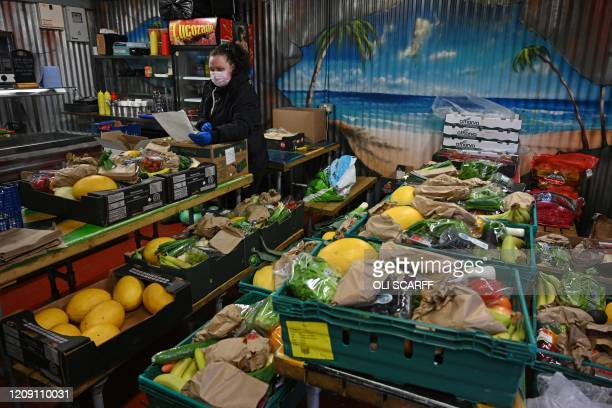Lisa McCall selects produce for free deliveries to her customers of fruit and veg in her greengrocer shop in Manchester northwest England on April 4...