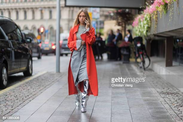 Lisa Olsson wearing striped long shirt red coat silver boots grey skirt outside Valerie on August 31 2017 in Stockholm Sweden