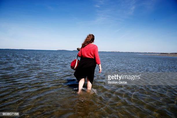 Lisa Quigley of Somerville wades into the water at Wollaston Beach in Quincy MA on April 24 2018