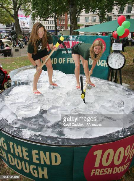 Lisa Raynsford and Tabatha Williams from Papa John's pizza delivery company destroy a giant pizza ice sculpture in London's Leicester Square today to...