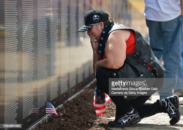 Lisa Swartz, of Denver, pauses at the traveling Vietnam Wall at Furniture Row in Dacono Thursday. Swartz had found the name of a serviceman that was...