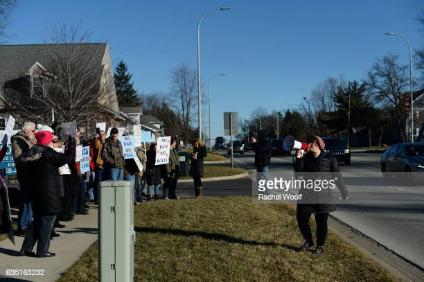 Lisa Weaver of South Lyon Mich speaks in a loudspeaker as she protests outside of Republican Rep Mike Bishop's office on February 13 2017 in Brighton...