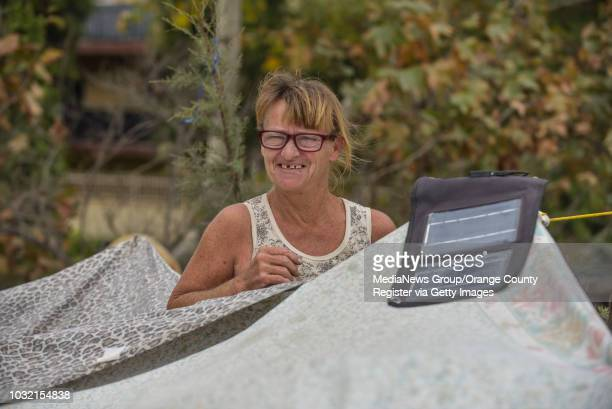 Lisa Weber uses a solar panel to charge a cell phone at her tent along the west side of the Santa Ana River south of Edinger Avenue in Unincorporated...