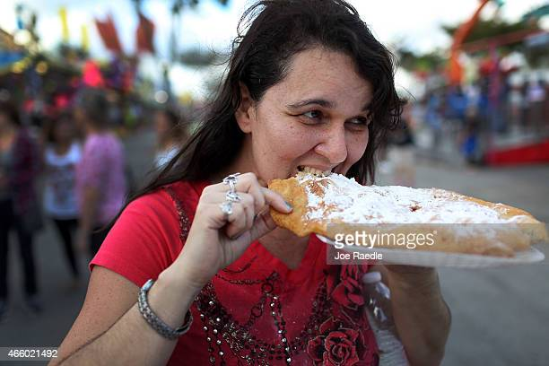 Lisandra Miller bites into a funnel cake on the first day of the MiamiDade County Youth Fair at Tamiami Park on March 12 2015 in Miami Florida The...