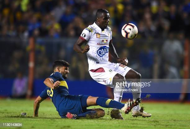 Lisandro Lopez of Boca Juniors fights for the ball with Marco Perez of Deportes Tolima during a group G match between Boca Juniors and Deportes...