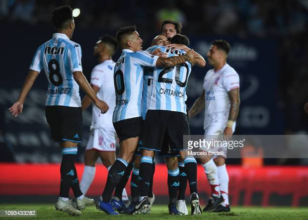 Lisandro Lopez of Racing Club celebrates with teammates after scoring the second goal of his team during a match between Racing Club and Huracan as...
