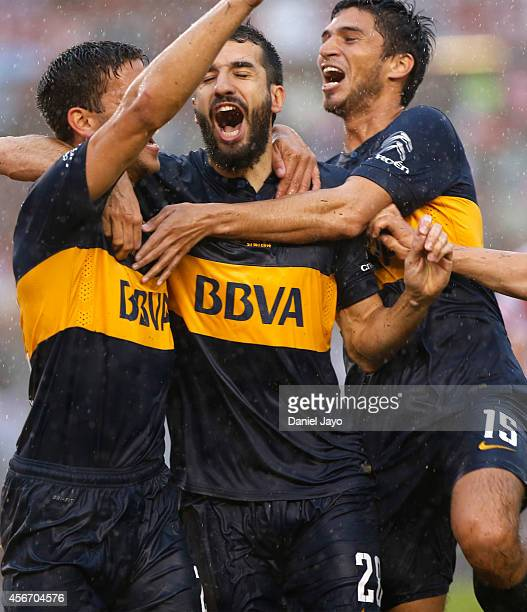 Lisandro Magallan of Boca Juniors celebrates with his teammates Mariano Echeverria and Leandro Marin after scoring the first goal of his team during...