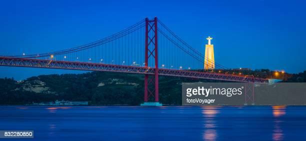 lisbon 25 de abril bridge over tagus illuminated dusk portugal - statua di cristo re foto e immagini stock