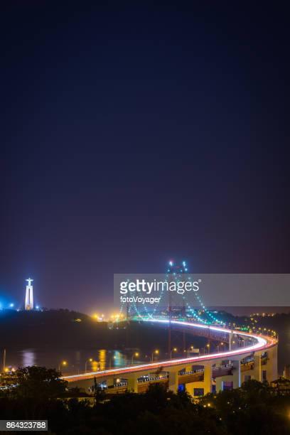 lisbon night lights illuminating ponte 25 de abril bridge portugal - statua di cristo re foto e immagini stock