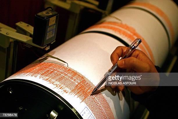 Portuguese seismologist Carlos Corela shows on a seismograph of the Instituto Geofisico in Lisbon 12 February 2007 the moment where an earthquake...