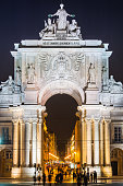 Lisbon Rua Augusta Arch illuminated at dusk above crowds Portugal