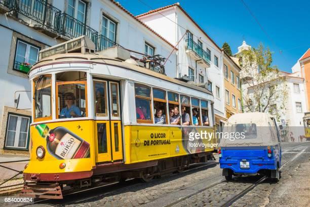 Lisbon tourists enjoying ride on iconic yellow tram Alfama Portugal