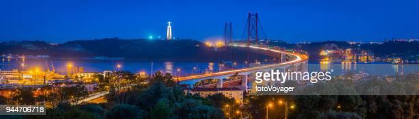 lisbon waterfront 25 de abril bridge illuminated night panorama portugal - statua di cristo re foto e immagini stock