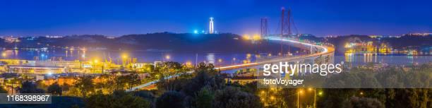 lisbon waterfront landmarks harbour bridge illuminated at night panorama portugal - statua di cristo re foto e immagini stock