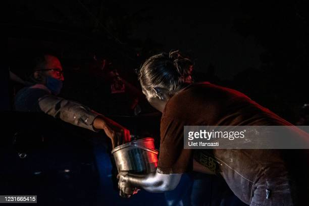 Lisda , has five children and is six months pregnant wearing silver paint begging on the street on March 10, 2021 in Depok, Indonesia. Lisda, was...
