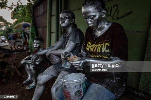 Lisda , has five children and is six months pregnant wearing silver paint hold money from begging on the street on March 10, 2021 in Depok,...