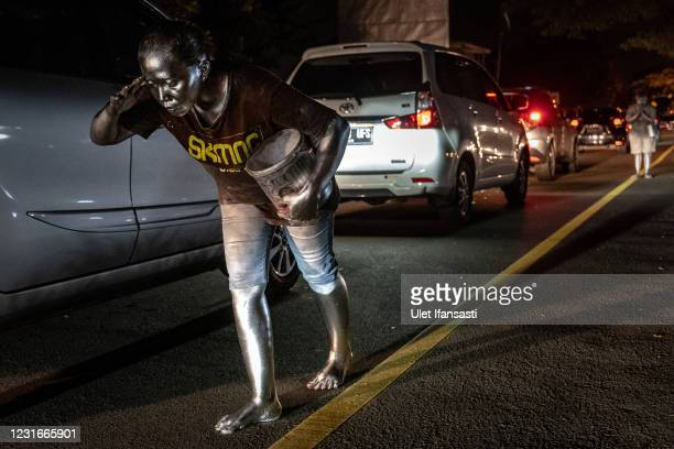 Lisda , has five children and is six months pregnant wearing silver paint beg on the street on March 10, 2021 in Depok, Indonesia. Lisda, was have a...