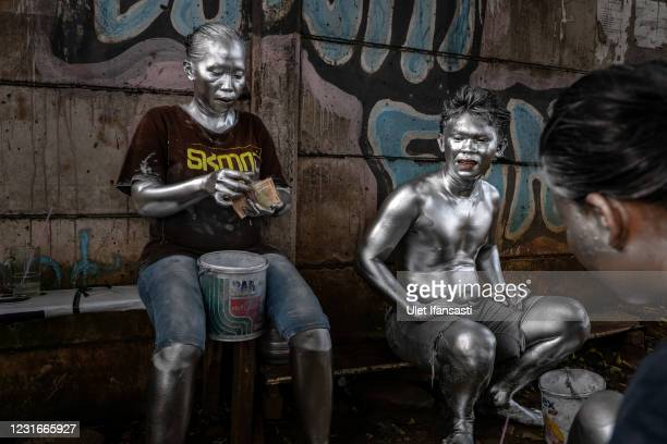 Lisda , has five children and is six months pregnant wearing silver paint hold money from beg on the street on March 10, 2021 in Depok, Indonesia....
