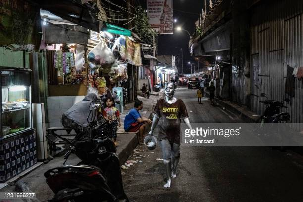 Lisda , has five children and is six months pregnant wearing silver paint walking as way home from beg on the street on March 10, 2021 in Depok,...