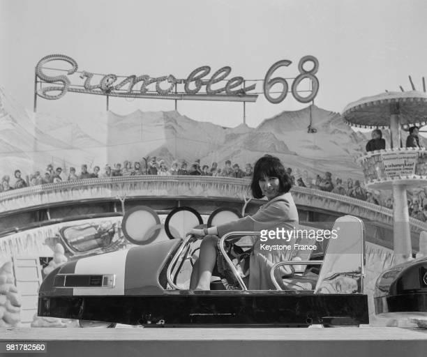 Lise Sarian assise dans un bobsleigh dans le manège 'Grenoble 68' à la Foire du Trône sur la pelouse de Reuilly à Paris en France le 17 mars 1967