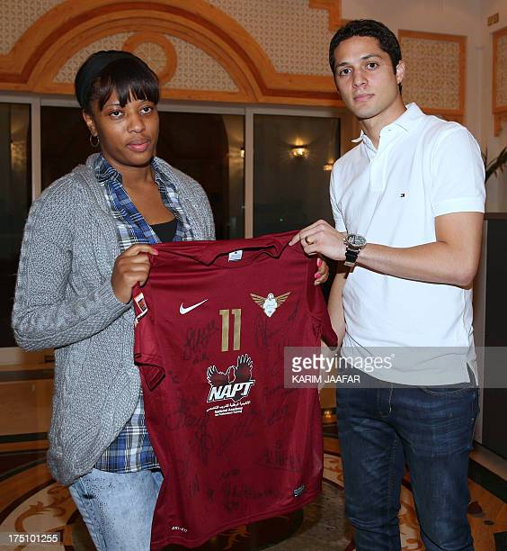 Liseth Chala the wife of Ecuadorian striker Christian 'Chucho' Benitez holds her husband's strip which was given to her by Brazilian player Anderson...