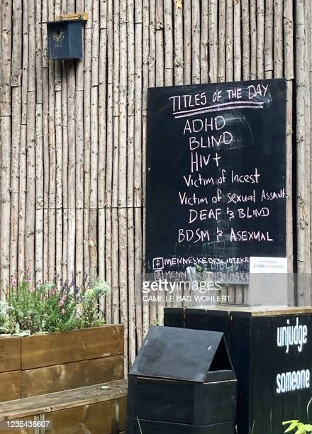 List of titles of 'human books' is seen on a blackboard at the Human Library in Copenhagen on August 29, 2021. - At the 'Human Library', you can...