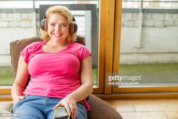 listening at home. - blond mollig frau stock-fotos und bilder