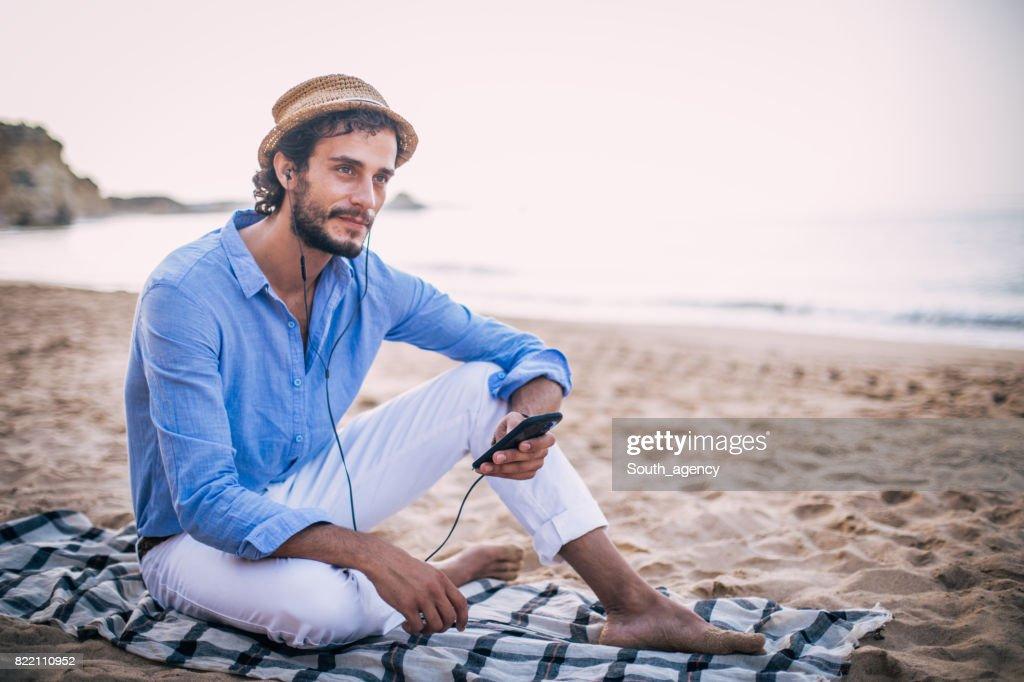 Listening music at coastline : Stock Photo