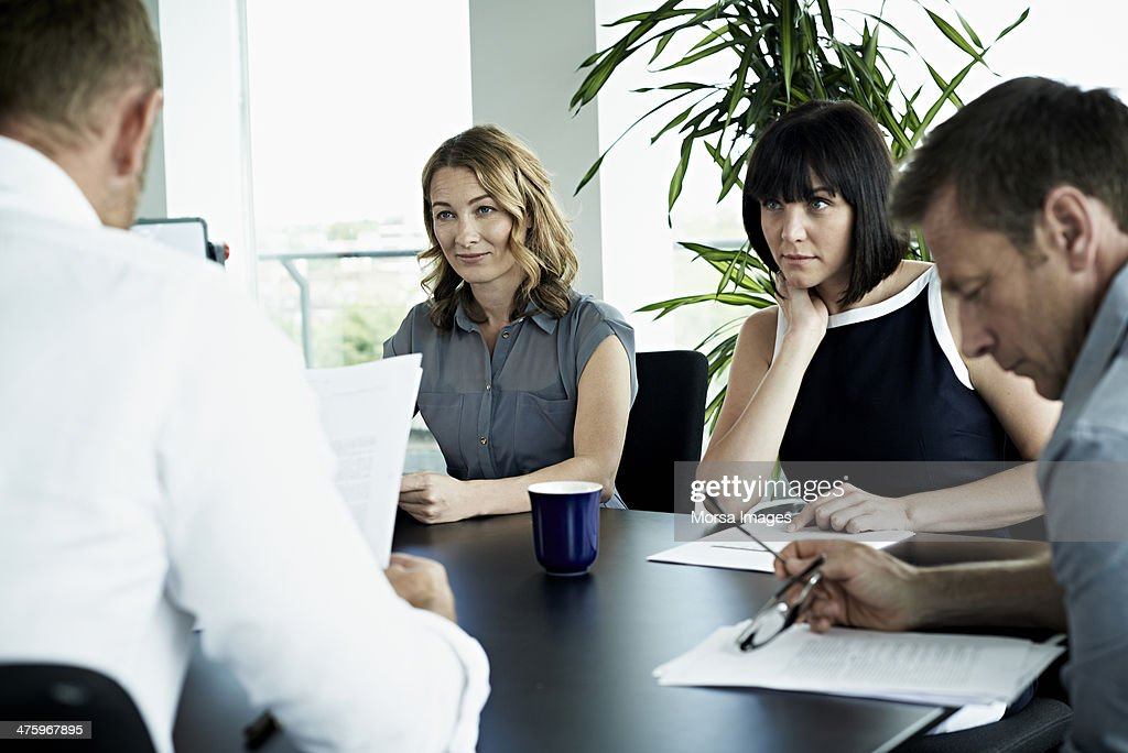 Listening to coworker explain report : Stock Photo