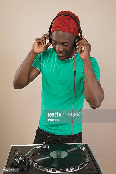 A DJ listening to headphones in front of turntable