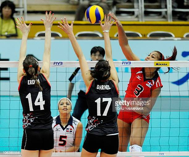Lisvel Elisa Eve Mejia of the Dominican Republic spikes the ball over Eda Erdem and Neslihan Darnel of Turkey while her teammate Brenda Castillo...