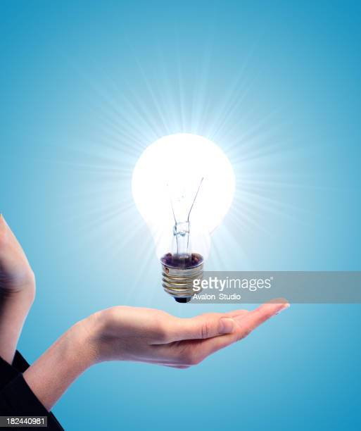 Lit bulb and the woman's hand on a blue background