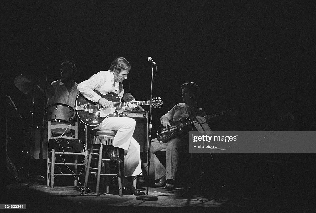 Lit by a stage light, country musician Chet Atkins sits in front of his drummer and bassist, playing his electric guitar.