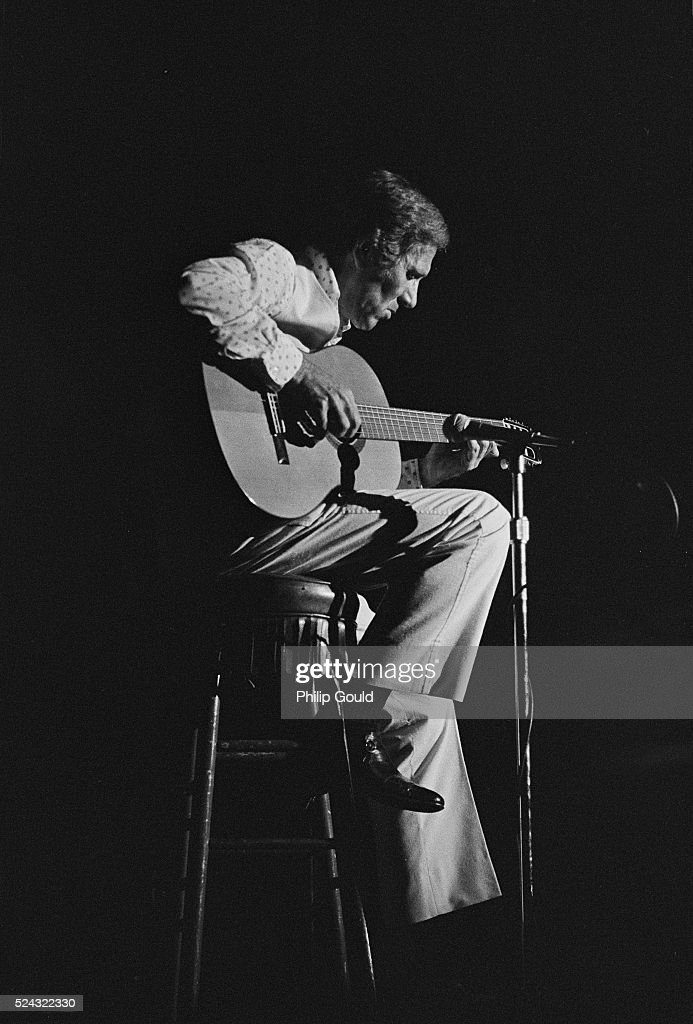 Lit by a stage light, country musician Chet Atkins sits on a stool strumming his acoustic guitar.